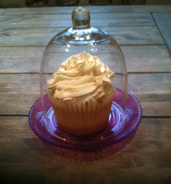 White fronsted cupcake in glass case
